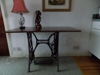 Old cast iron Singer sewing machine treadle now table.