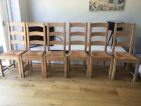 6 pine dining room chairs for sale. Great condition! Solid pine high ladder back and wicker seats