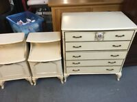 A FRENCH STLE CREAM CHEST OF FIVE DRAWERS WITH A PAIR OF MATCHING BEDSIDE CABINETS
