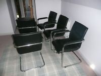 Set of five cantilever dining chairs with armrests.