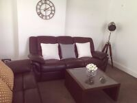 Two Faux Leather Recliner Sofas and a Coffee Table up for sale