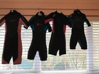 Four children's wetsuits.