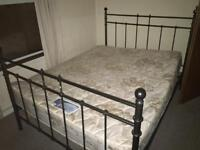 Double bed with black frame and mattress