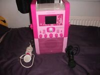 pink karaoke machine with screen, graphics and lots of discs (ono)