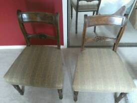 A pair of Padded regency dining chairs .
