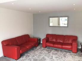 Red leather three seater sofas