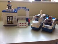 Duplo police station with two police vehicles.