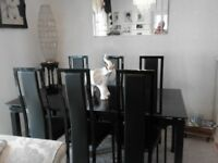 Black glass extending dining table and six chairs