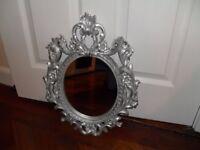 Oval mirror with rococo style wood silver sprayed frame. 35 cm x 45 cm. Black felt back, with hook