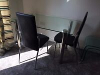 Glass table and 4 black and chrome leather look chairs