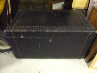 OLD WOOD TRUNK COVERD IN BLACK LEATHERETTE FABRIC WITH STUD DETAIL ON CASTERS IN GOOD CONDITION £35