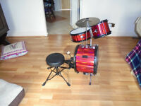 Small childs drum kit as knew, red and blcak has a foot pedle and stool.