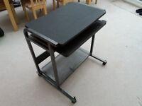 Black computer desk on castors