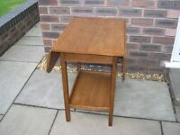 A solid oak drop leaf table with under tier.