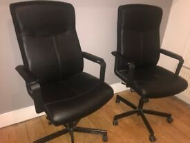 Two black Ikea swivel office chairs for sale.