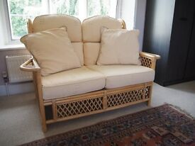 Honey Coloured Cane Conservatory 2 seater plus 2 single chairs with soft yellow upholstery.