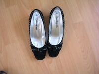 Black wedge shoes with white stitched pattern, size 5.