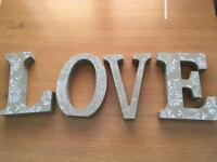 Large Love Letters. Used as wedding decoration. White flowers detail.