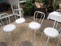 four white kitchen chairs