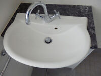 White ceramic wash basin with mixer taps
