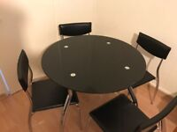 Round black glass dining table with 4 chairs