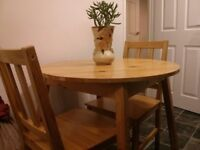 Wooden round table + two wooden chairs.