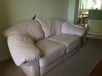 Two seater cream faux leather sofa in good condition