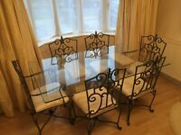 Tempered glass table with 4 chairs and 2 carvers and a glass sideboard.