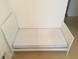 White cotbed and mattress