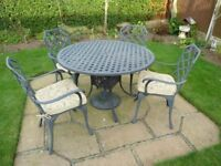 Cast alloy table and 4 matching chairs with cushions