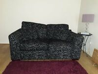 Lovely 2-Seater Sofa for sale. Black with Grey swirly Rose pattern.