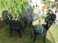 black metal garden table and three black metal garden chairs