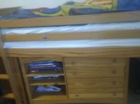 single bed with shelves and side table and drawer