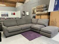 Large grey corner sofa with footstool