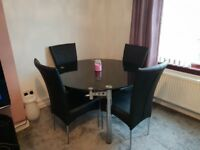 Black glass extending dining table & 4 black leather chairs
