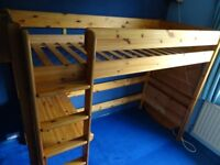 Single highrise pine bed. Like a top bunk without a bottom one, so the space underneath can be used.