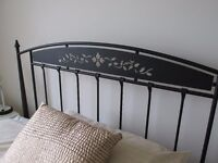 Double bed frame in black wrought iron with sprung slatted base.