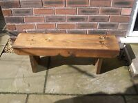 A wooden garden bench with single scallop trim.