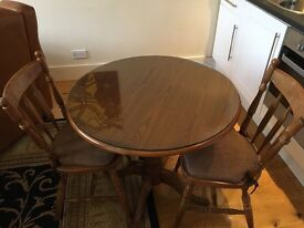 Small wooden round table with removable glass top. Plus 2 chairs with cushions.