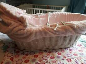 Pink and white wicker moses basket