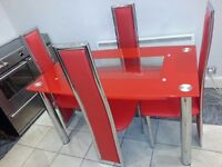 Lovely large red glass dining table and 4 chairs. excellent condition