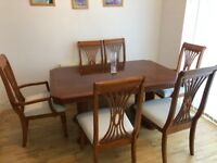Solid brown extending dining table and 6 chairs. 2m long when extended.