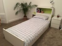 white single bed with separate headboard with open shelves and hidden pull-out storage unit