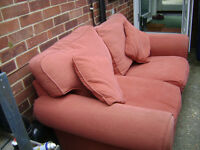 Nice little 2 seater sofa in a terracota colour, in good condition -see pictures. Matching cushions.