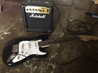 Squier mini fender guitar with strap and Marshall amplifier.