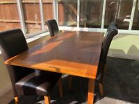 Oak dining table with four leather chairs