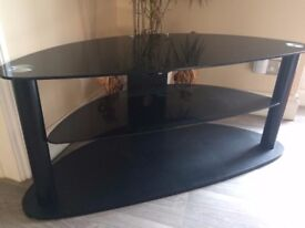 Black glass and wood TV stand measures 48 inches wide