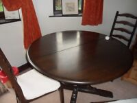 Dark wood Ercol pedestal table and four chairs