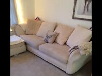 A large cream sofa and a glass dining table including two leather chairs