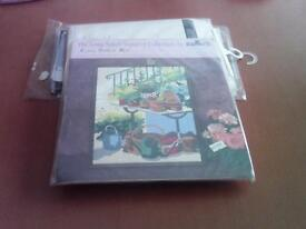New long stitch tapestry kit called Potting Time.Picture is of a potting table with pots etc.